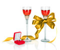 Wine in two wineglasses with golden satin  bow and wedding rings Royalty Free Stock Photo