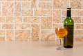 Wineglass on brick background wine bottle and glass wall Stock Images
