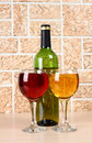 Wineglass on stone background wine bottle and glass brick wall Royalty Free Stock Images