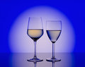 Wineglass with white wine on blurred blue  background Royalty Free Stock Photo