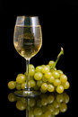 Wineglass with white wine and grapes on a black background Royalty Free Stock Photos
