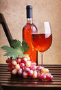 Wineglass, wine bottles and grapes Royalty Free Stock Images
