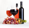 Wineglass, wine bottles and grapes Stock Photography