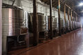 Winery large room a corridor with steel barrels containing white wine inside a in chile vale del colchagua and wood poles Stock Photo
