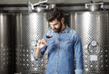 Winery owner portrait of at work young professional winemaker standing in front of stainless steel vessel while tasting a glass of Stock Images