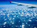 Wing of an airplane and clouds white fluffy Royalty Free Stock Photo