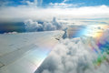 Wing of airplane flying above clouds in the sky Royalty Free Stock Photo