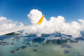 Wing of the plane with blue sky and cloud over island sea Stock Image