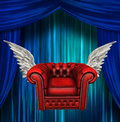 Winged comfort chair before blue curtains Stock Photography