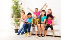 Wining in video game close portrait of a group of diversity looking kids boys and girls playing videogame sitting on the couch Royalty Free Stock Images