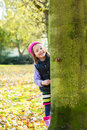 Wink a little girl behind a tree winking Stock Image