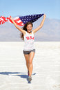 Winner athlete woman with american flag usa running and t shirt runner girl showing winning gesture excited and happy outdoor in Stock Photo