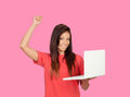 Winner girl with a laptop on pink background Stock Photos