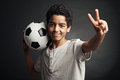 Winner portrait of young boy with a soccer ball signing victory Royalty Free Stock Image