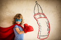 Winner superhero kid in red boxing gloves punching on the drawn bag and success concept Royalty Free Stock Images