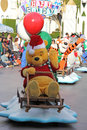 Winnie the pooh riding a sled during a disneyland christmas parade Stock Images