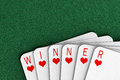 Winning hand playing cards on a felt table spelling out the word winner Stock Images