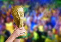 Winning soccer world cup hands holding fifa trophy on multicolor faded stadium background Stock Photography