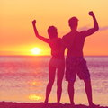 Winning success concept happy beach couple at sunset with arms raised up outstretched cheering and beautiful young fitness Stock Photography