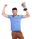 Winning young casual man with a big trophy cup and hands in the air Royalty Free Stock Image