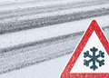 Winter background tire tracks driving snowy road with and warning sign Stock Photos