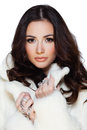 Winter beauty young brunette lady in white fur coat posing on white background Royalty Free Stock Photography