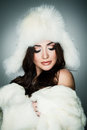 Winter beauty young brunette lady in white fur hat posing on grey background Royalty Free Stock Photography