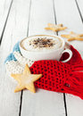 Winter cappuccino coffee in white cup with christmas cookies a star shaped and warm scarf on planked wood background rural still Royalty Free Stock Images
