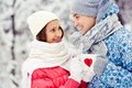 Winter cheers portrait of happy young couple holding cups with red hearts and toasting in park Royalty Free Stock Photo