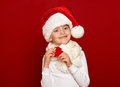 Winter child christmas concept happy girl in santa hat show fir tree wool toy on red background Royalty Free Stock Photo