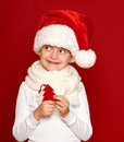 Winter child christmas concept happy girl in santa hat show fir tree wool toy on red background Stock Photos