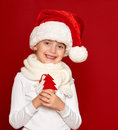 Winter child christmas concept happy girl in santa hat show fir tree wool toy on red background Stock Photography