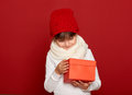 Winter, child,  christmas holiday concept - happy girl in hat with box gift on red Royalty Free Stock Photo