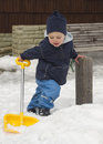 Winter child with snow shovel shoveling a in front of a house yellow in Stock Image