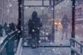 Winter city street and snow. Person standing alone. Blurred imag Royalty Free Stock Photo