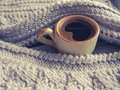Winter coffee. Cup of black coffee in a knitted sweater. Toning.