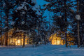 Winter cold night, small wooden houses with warm light Royalty Free Stock Photo