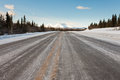 Winter on country road in taiga and snowy mountain Stock Images
