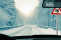 Winter driving snowy country road in and warning sign risk of snow and ice Royalty Free Stock Photo