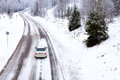 Winter driving white car snow covered road conditions Stock Images