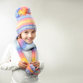 Winter fashion portrait of girl in knitted hat and scarf on a light background Royalty Free Stock Photo