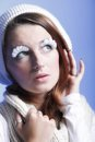Winter fashion woman warm clothing creative makeup beautiful in stylish make up false long white eye lashes blue background Stock Photos
