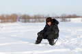 Winter fisherman sitting with fishing rod Stock Image