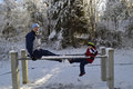 Winter fun father and son on the parallel bars in the park competing with each other who is stronger Royalty Free Stock Photos
