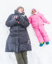 Winter fun a mother and child lying in snow having during season Stock Images