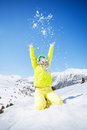 Winter fun in mountains cute happy young woman green ski outfit throwing snow the air Stock Photo