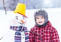 Winter fun my friend snowman and me smiling with bucket striped scarf little cheerful boy kid are standing on background happy Royalty Free Stock Photo