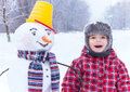 Winter fun my friend snowman and me are in the winter snow day smiling cute with yellow bucket striped scarf little cheerful boy Royalty Free Stock Photo