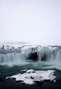 Winter at godafoss waterfall in iceland full shot of north east with a cross section of tones purples and blues and icicle caves Royalty Free Stock Image