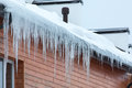 Winter hanging icicles house roof Royalty Free Stock Photo